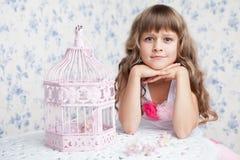 Τρυφερό ονειροπόλο ρομαντικό κορίτσι κοντά στο ανοικτό birdcage Στοκ Φωτογραφία