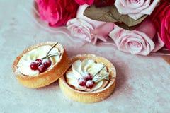 Τρυφερό ρομαντικό δώρο: γλυκά κέικ με την κρέμα και τα μούρα και μια ανθοδέσμη των ρόδινων τριαντάφυλλων σε ένα ελαφρύ υπόβαθρο στοκ εικόνα