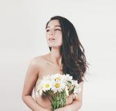 Τρυφερό χαριτωμένο όμορφο θερινό νέο κορίτσι με το τόπλες τέλειο δέρμα σωμάτων κρατά camomiles τα λουλούδια Άσπρη ανασκόπηση στοκ φωτογραφίες