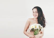 Τρυφερό χαριτωμένο όμορφο θερινό νέο κορίτσι με το τόπλες τέλειο δέρμα σωμάτων κρατά camomiles τα λουλούδια Άσπρη ανασκόπηση στοκ φωτογραφία με δικαίωμα ελεύθερης χρήσης