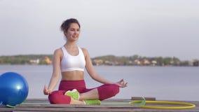 Τρόπος ζωής γιόγκας, όμορφη γυναίκα γιόγκη στη θέση λωτού meditates και σπιρίτσουαλ απολαύσεων calmnes κοντά στο νερό απόθεμα βίντεο