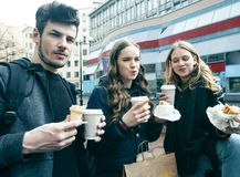 Τρόπος ζωής και έννοια ανθρώπων: δύο κορίτσια και τύπος που τρώνε το γρήγορο φαγητό στην οδό πόλεων μαζί που έχει τη διασκέδαση,  στοκ φωτογραφίες με δικαίωμα ελεύθερης χρήσης