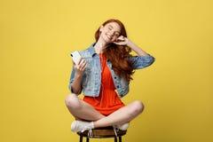 Τρόπος ζωής, μουσική, έννοια τεχνολογίας: Νέα όμορφη καυκάσια μουσική ακούσματος γυναικών με τα ακουστικά και το έξυπνο τηλέφωνο Στοκ Φωτογραφία