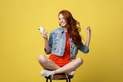 Τρόπος ζωής, μουσική, έννοια τεχνολογίας: Νέα όμορφη καυκάσια μουσική ακούσματος γυναικών με τα ακουστικά και το έξυπνο τηλέφωνο Στοκ εικόνες με δικαίωμα ελεύθερης χρήσης