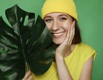 Τρόπος ζωής, συγκίνηση και έννοια ανθρώπων: Χαμογελώντας όμορφη γυναίκα πίσω από το μεγάλο φύλλο στοκ φωτογραφίες