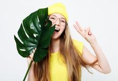 Τρόπος ζωής, συγκίνηση και έννοια ανθρώπων: Χαμογελώντας όμορφη γυναίκα πίσω από το μεγάλο φύλλο στοκ φωτογραφία