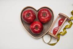 τρόφιμα έννοιας υγιή ικανότητα σιτηρεσίου Ρολόι γυαλιού και η κόκκινη Apple στο ξύλινο κιβώτιο μορφής καρδιών μέτρηση της ταινίας Στοκ Εικόνες