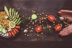 τρόφιμα έννοιας υγιή Χέρια και υγιής σαλάτα με chickpea και λαχανικά στον ξύλινο πίνακα Τρόφιμα Vegan χορτοφάγος σιτηρεσίου Στοκ φωτογραφία με δικαίωμα ελεύθερης χρήσης