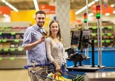 Τρόφιμα αγοράς ζεύγους στο παντοπωλείο στον κατάλογο μετρητών στοκ εικόνα με δικαίωμα ελεύθερης χρήσης