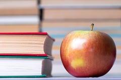 Τρόφιμα και βιβλία, κόκκινο μήλων δίπλα στα βιβλία που συσσωρεύονται σε μια σειρά Στοκ εικόνες με δικαίωμα ελεύθερης χρήσης
