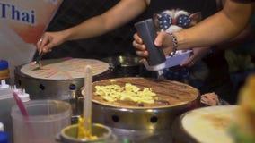 Τρόφιμα οδών: Το ταϊλανδικό άτομο κάνει τις τηγανίτες με τις μπανάνες και τη σοκολάτα στην αγορά τροφίμων νύχτας απόθεμα βίντεο