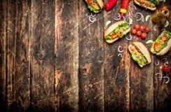 Τρόφιμα οδών Χοτ-ντογκ με τη μουστάρδα, την καυτή σάλτσα, το κρεμμύδι και τα πράσινα Στοκ εικόνες με δικαίωμα ελεύθερης χρήσης