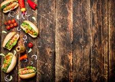 Τρόφιμα οδών Χοτ-ντογκ με τη μουστάρδα, την καυτή σάλτσα, το κρεμμύδι και τα πράσινα Στοκ Εικόνα