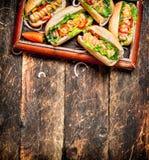 Τρόφιμα οδών Χοτ-ντογκ με τη μουστάρδα, την καυτή σάλτσα, το κρεμμύδι και τα πράσινα Στοκ Φωτογραφία