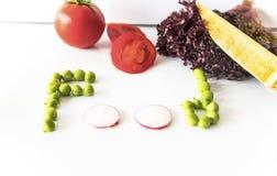 Τρόφιμα που γράφουν με τα πράσινα μπιζέλια και το κόκκινο ραδίκι στο απομονωμένο υπόβαθρο με το μαχαίρι μπαμπού στοκ φωτογραφία