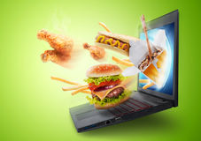 Τρόφιμα που πετούν από μια οθόνη lap-top Στοκ Εικόνα