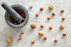 Τρόφιμα που τίθενται με τα διάφορα καρύδια για την παραγωγή των καρυκευμάτων και του υποβάθρου πετρών κονιάματος τη τοπ άποψη Στοκ Φωτογραφίες