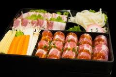 Τρόφιμα της Κορέας στο εστιατόριο, το φρέσκο τεμαχισμένο σύνολο χοιρινού κρέατος και το μικτό λαχανικό που τίθενται στο μαύρο υπό Στοκ Φωτογραφίες