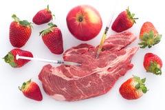 τρόφιμα τροποποιημένα μήλο, βόειο κρέας και φράουλες σε ένα άσπρο υπόβαθρο με τις σύριγγες Στοκ φωτογραφία με δικαίωμα ελεύθερης χρήσης