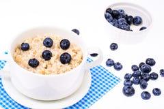 τρόφιμα υγιή Oatmeal κουάκερ με τα βακκίνια στην μπλε πετσέτα Στοκ εικόνα με δικαίωμα ελεύθερης χρήσης