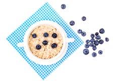τρόφιμα υγιή Oatmeal κουάκερ με τα βακκίνια στην μπλε πετσέτα Στοκ φωτογραφία με δικαίωμα ελεύθερης χρήσης