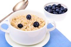 τρόφιμα υγιή Oatmeal κουάκερ με τα βακκίνια στην μπλε πετσέτα Στοκ Εικόνα