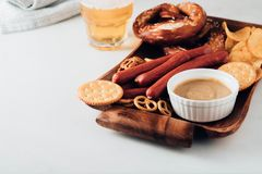 Τρόφιμα Oktoberfest, ορεκτικά πρόχειρα φαγητά μπύρας που τίθενται για τη μεγάλη επιχείρηση Ψημένα στη σχάρα λουκάνικα, τσιπ, pret Στοκ Εικόνες