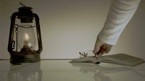 Τρύγος κινηματογράφος παλαιός πίνακας γυαλιού με τα βιβλία και την κηροζίνη Lamrim το χέρι βάζει στο βιβλίο γυαλιών απόθεμα βίντεο