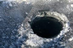 Τρύπα αλιείας πάγου με το μαύρο νερό Στοκ φωτογραφία με δικαίωμα ελεύθερης χρήσης