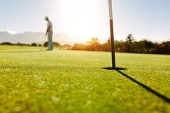Τρύπα και σημαία γκολφ στον πράσινο τομέα με τον παίκτη γκολφ στοκ φωτογραφίες
