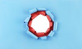 Τρύπα στο μπλε και κόκκινο έγγραφο Στοκ φωτογραφίες με δικαίωμα ελεύθερης χρήσης