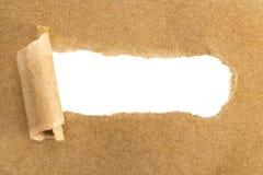 Τρύπες στο καφετί έγγραφο με τις σχισμένες πλευρές πέρα από το υπόβαθρο εγγράφου με στοκ φωτογραφίες
