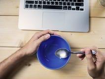 Τρώγοντας στο γραφείο εργασίας, κενό κύπελλο στοκ φωτογραφίες