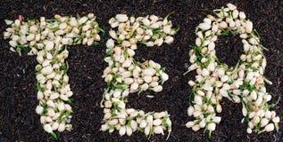 Τσάι λέξης φιαγμένο από ξηρούς jasmine οφθαλμούς λουλουδιών πέρα από τα μαύρα φύλλα τσαγιού Στοκ Φωτογραφία