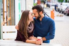 Τσάι ή καφές κατανάλωσης ανδρών και γυναικών Πικ-νίκ Ποτό θερμό στο δροσερό καιρό Ευτυχές ζεύγος με τα φλυτζάνια καφέ στο πάρκο φ Στοκ φωτογραφία με δικαίωμα ελεύθερης χρήσης