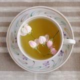 Τσάι ανθών της Apple στο άσπρο φλυτζάνι στο μπεζ λινό Στοκ φωτογραφία με δικαίωμα ελεύθερης χρήσης