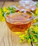 Τσάι από tutsan στο φλυτζάνι και teapot γυαλιού εν πλω Στοκ Εικόνες