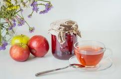 Τσάι, βάζο της μαρμελάδας σμέουρων και μήλα στον άσπρο πίνακα Στοκ φωτογραφία με δικαίωμα ελεύθερης χρήσης