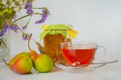 Τσάι, βάζο της μαρμελάδας της Apple και αχλάδια στον άσπρο πίνακα Στοκ Εικόνες