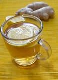 Τσάι λεμονιών με τα κομμάτια λεμονιών και πιπερόριζα στον πίνακα Στοκ φωτογραφία με δικαίωμα ελεύθερης χρήσης