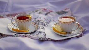 Τσάι λεμονιών στα φλυτζάνια στο ηλιοβασίλεμα απόθεμα βίντεο
