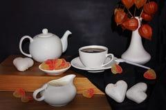 Τσάι και γλυκά με μορφή καρδιών στον πίνακα Στοκ Εικόνα