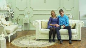 Τσάι κατανάλωσης ανδρών και γυναικών στον καναπέ φιλμ μικρού μήκους