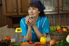 Τσάι κατανάλωσης γυναικών στην κουζίνα μεταξύ των λαχανικών στοκ φωτογραφίες