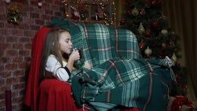 Τσάι κατανάλωσης κοριτσιών και κατοχή της διασκέδασης σε μια καρέκλα κοντά σε ένα χριστουγεννιάτικο δέντρο απόθεμα βίντεο