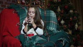 Τσάι κατανάλωσης κοριτσιών κινηματογραφήσεων σε πρώτο πλάνο που τυλίγεται σε ένα κάλυμμα κοντά σε ένα χριστουγεννιάτικο δέντρο απόθεμα βίντεο