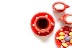 Τσάι καφέ στην κόκκινη κούπα με ένα φλυτζάνι του γάλακτος και της ζάχαρης και των καραμελών που απομονώνονται Στοκ φωτογραφία με δικαίωμα ελεύθερης χρήσης