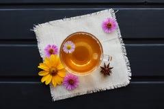 Τσάι λουλουδιών σε ένα διαφανές φλυτζάνι γυαλιού στο μαύρο πίνακα Θεραπεύοντας τσάι στοκ εικόνα με δικαίωμα ελεύθερης χρήσης