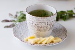 Τσάι μεντών φλυτζανιών στην παλαιά κούπα στο πιατάκι με το τυρί στοκ φωτογραφίες
