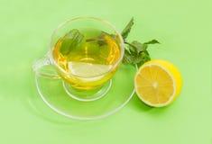 Τσάι με τη μέντα και λεμόνι σε ένα πράσινο υπόβαθρο Στοκ Φωτογραφία